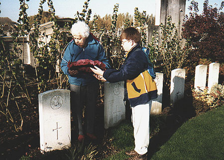 Phyllis Grace Geake (nee Weaver) placing a wreath on her father's grave with her great-grandson
